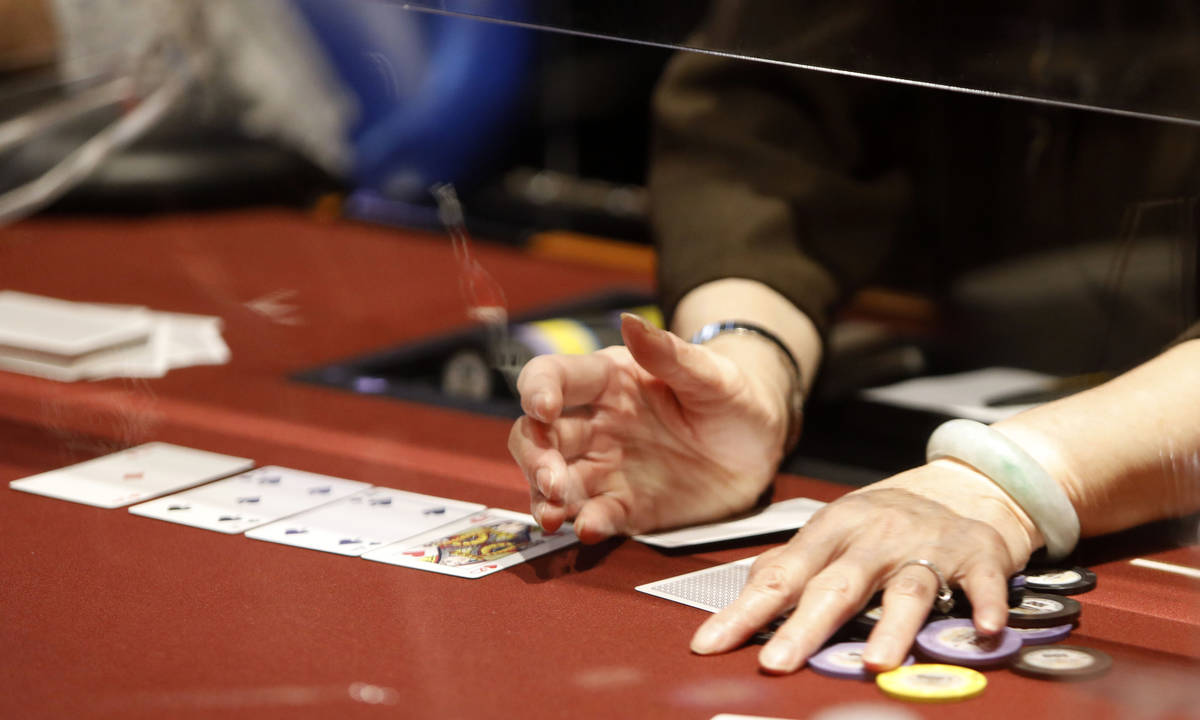 A dealer handles chips in $175 No-Limit Hold'em Ladies tournament during 2021 Nevada State Ladi ...