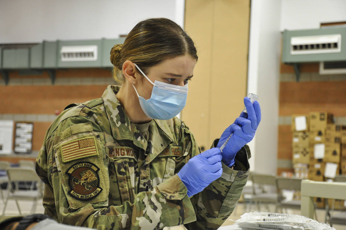 Caleena Longworth prepares a syringe with the Moderna vaccine at the Las Vegas Readiness Center ...