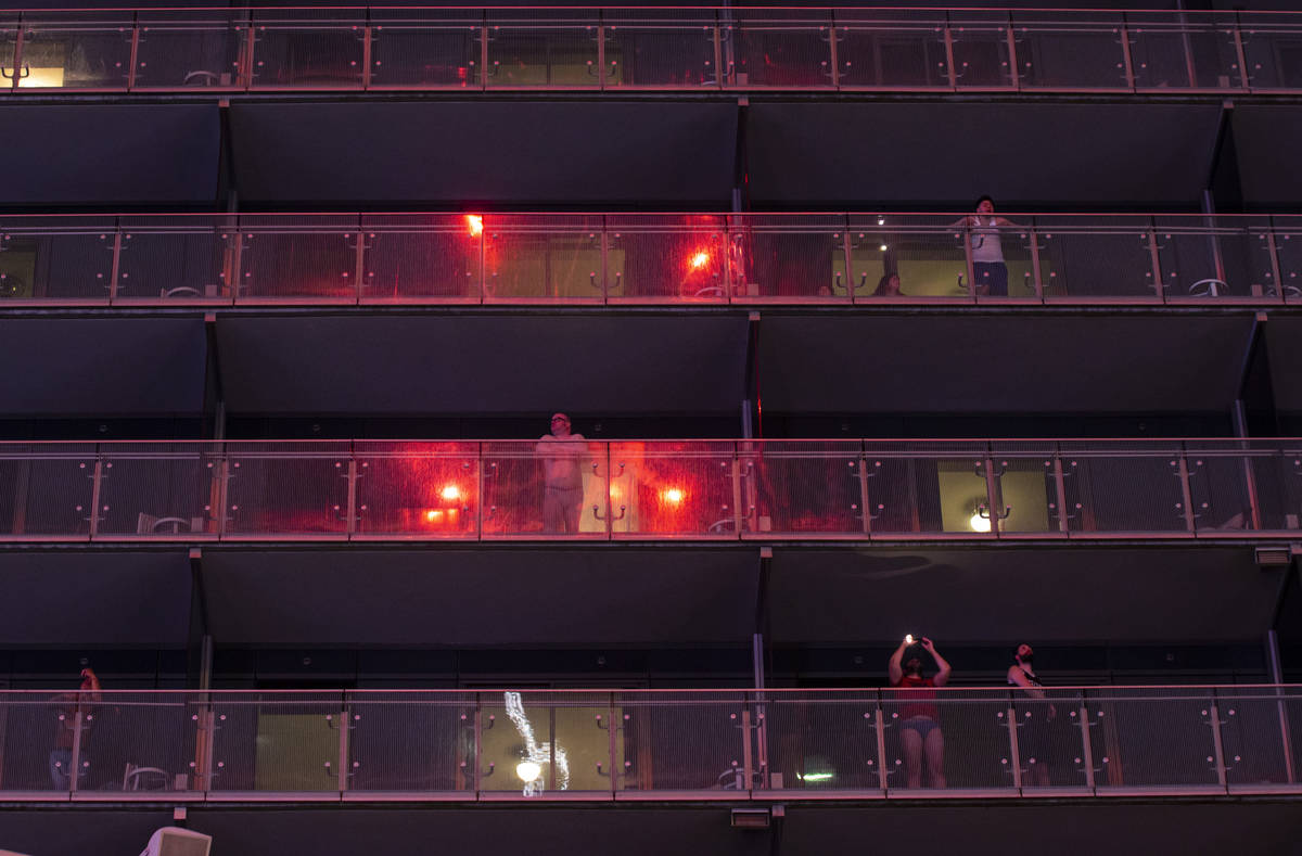 Fireworks are reflected in the balconies as people watch from The Cosmopolitan of Las Vegas on ...