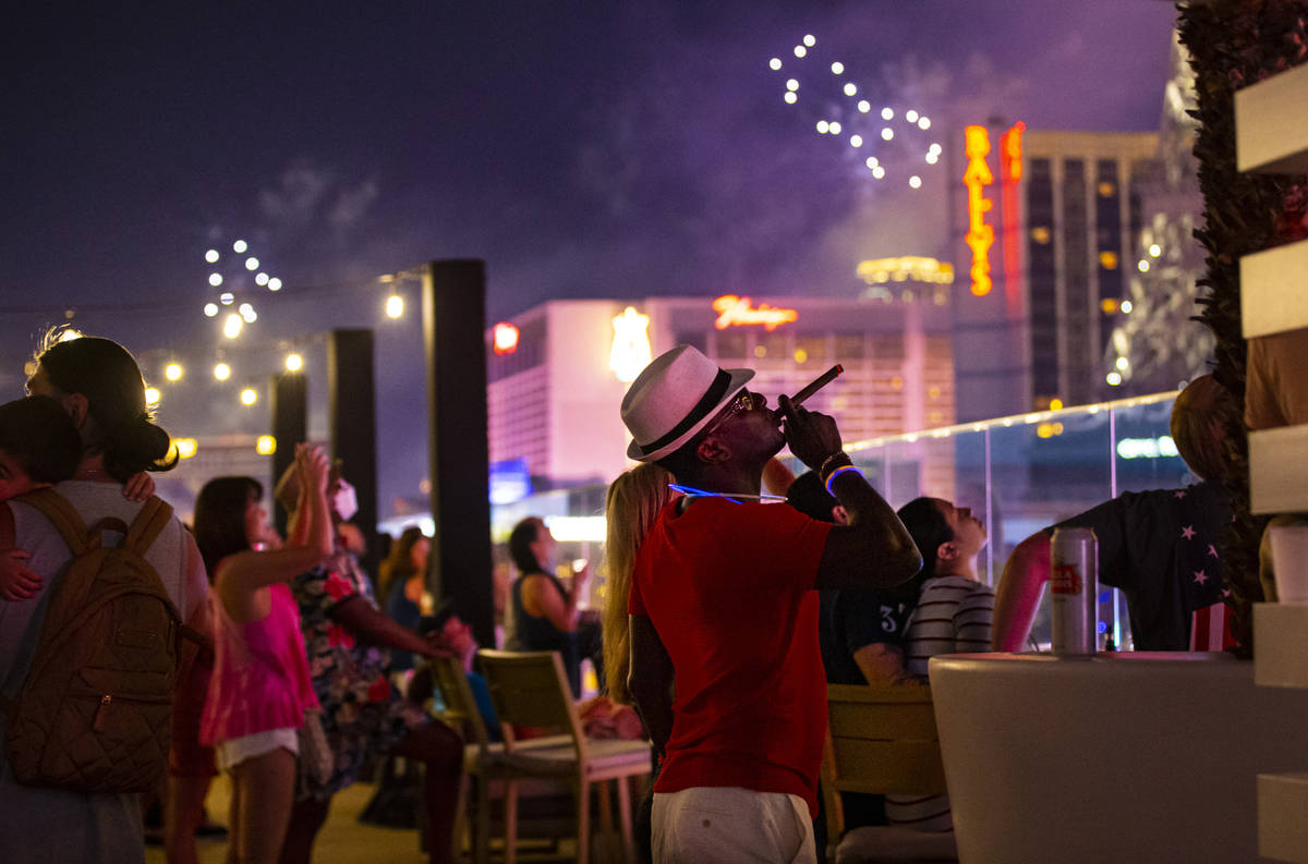 A man smokes a cigar while watching fireworks go off along the Las Vegas Strip from the Bouleva ...