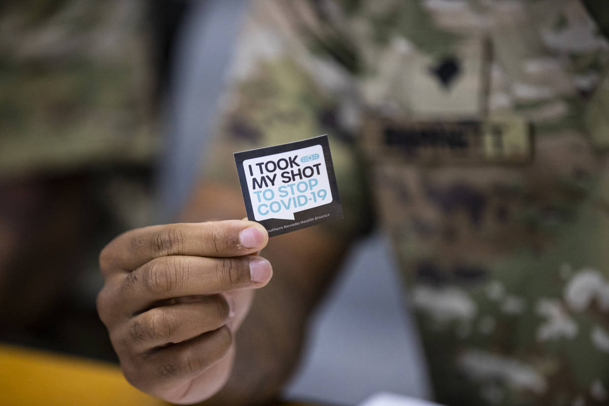 Nevada National Guard Spc. Demetrie Barnett holds up a sticker at his station at the vaccinatio ...