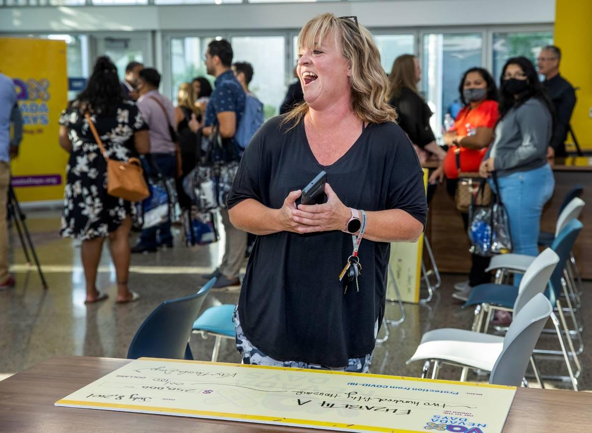 Teacher Elizabeth Allder laughs after calling her husband winning $250,000 as Governor Steve Si ...