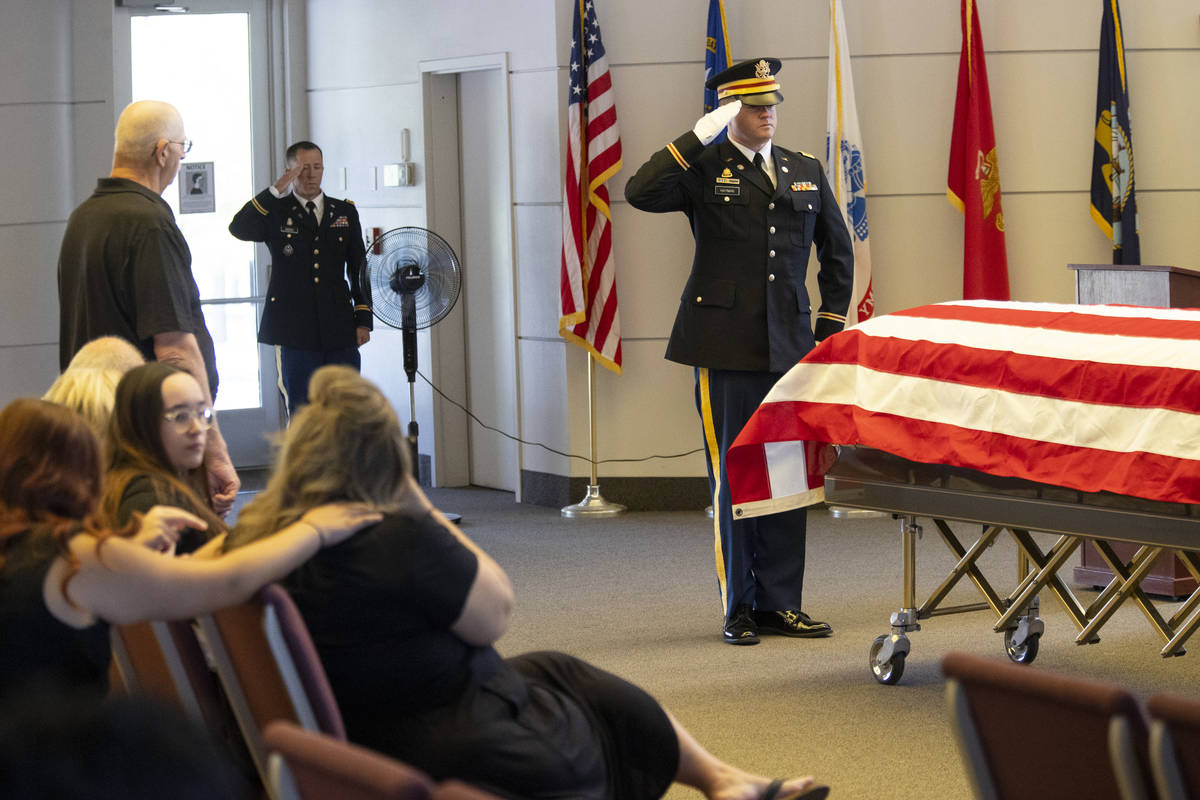 U.S. Army Lt. Kris Hayman salutes the flag-draped casket during a funeral service for retired N ...