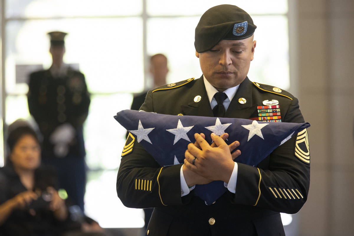 U.S. Army Master Sgt. Rafael Aguilera holds the American flag before presenting it to the famil ...