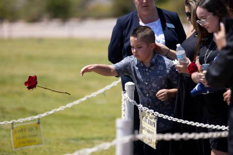 Noah Swanger, 8, tosses a rose on the gravesite of his father, Nevada National Guard member and ...