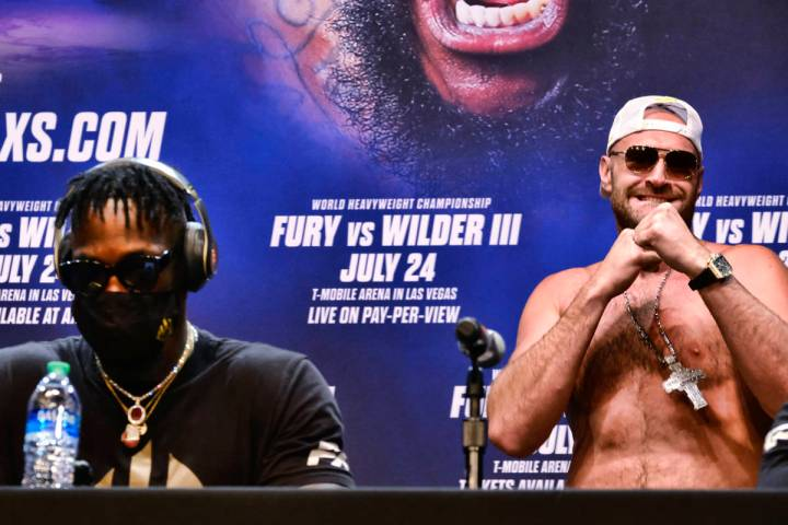 WBC heavyweight champion Tyson Fury, right, raises his fists as he walks near Deontay Wilder at ...