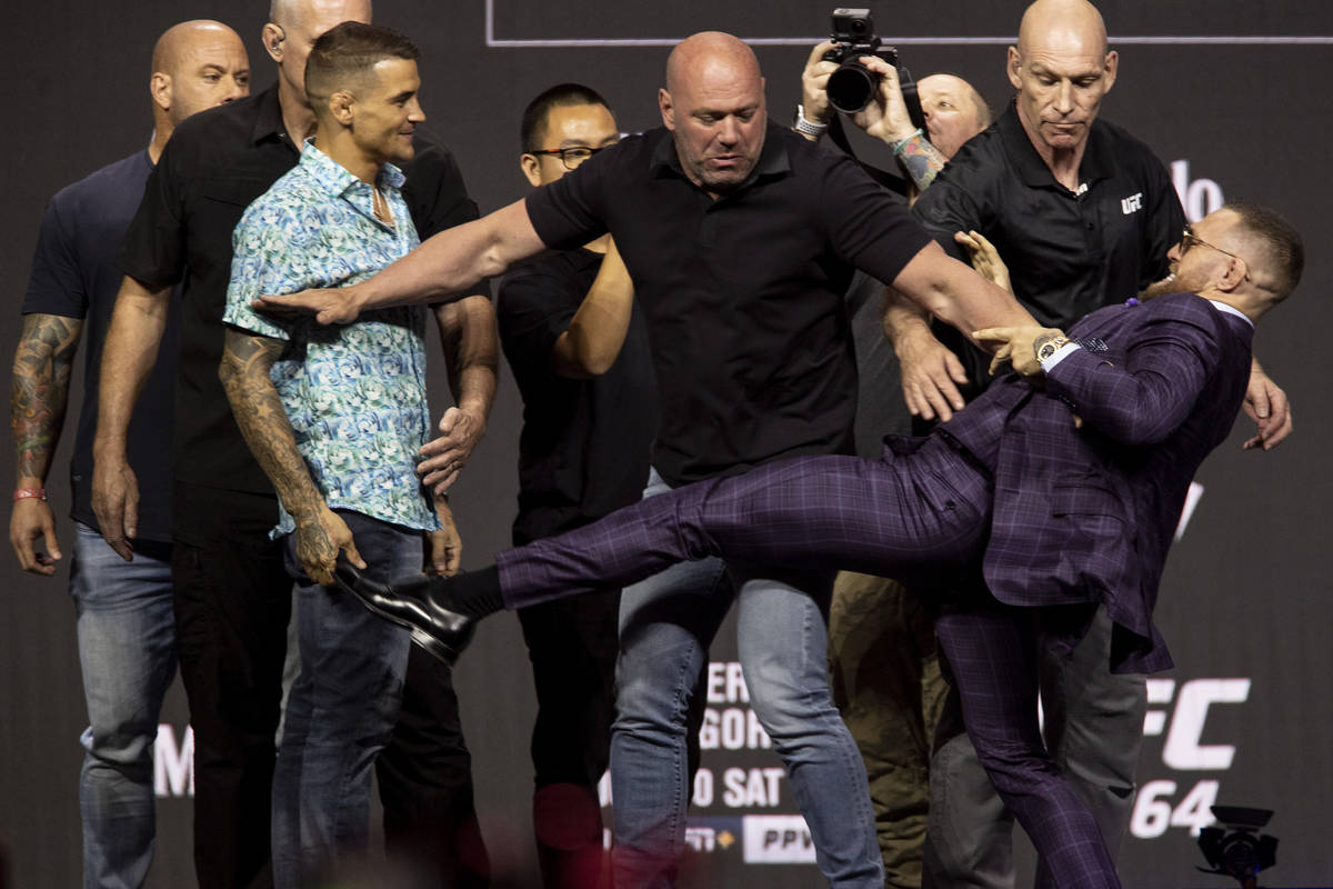 Dana White, center, stands between Dustin Poirier, left, and Conor McGregor during their face o ...