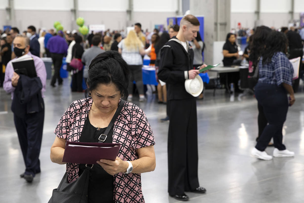 Job-seekers review the 14,000 positions available during a summer job fair hosted by Clark Coun ...