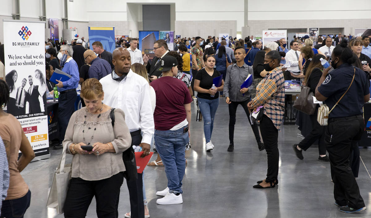 Job-seekers visit booths during a summer job fair hosted by Clark County, where 14,000 position ...