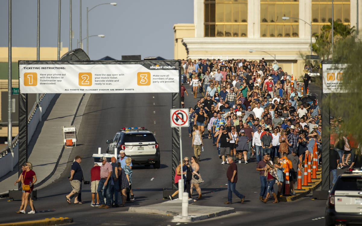 Fans make their way across the Hacienda overpass in the heat to the Garth Brooks concert at All ...