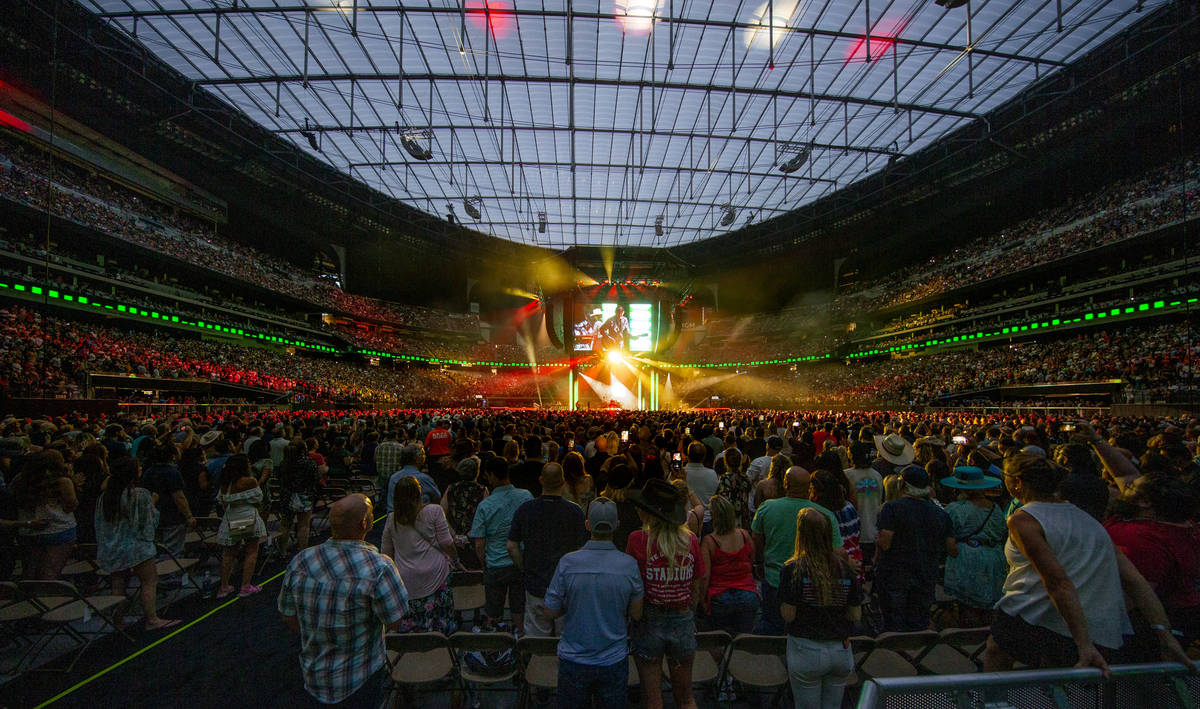 Fans stand and sing as Garth Brooks performs before the crowd at Allegiant Stadium on Friday, J ...