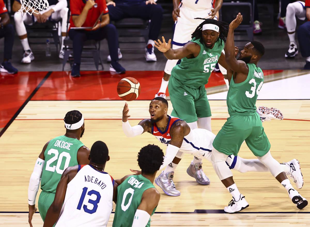 Damian Lillard (6) attempts a shot under pressure from NigeriaÕs Precious Achiuwa (55) and ...