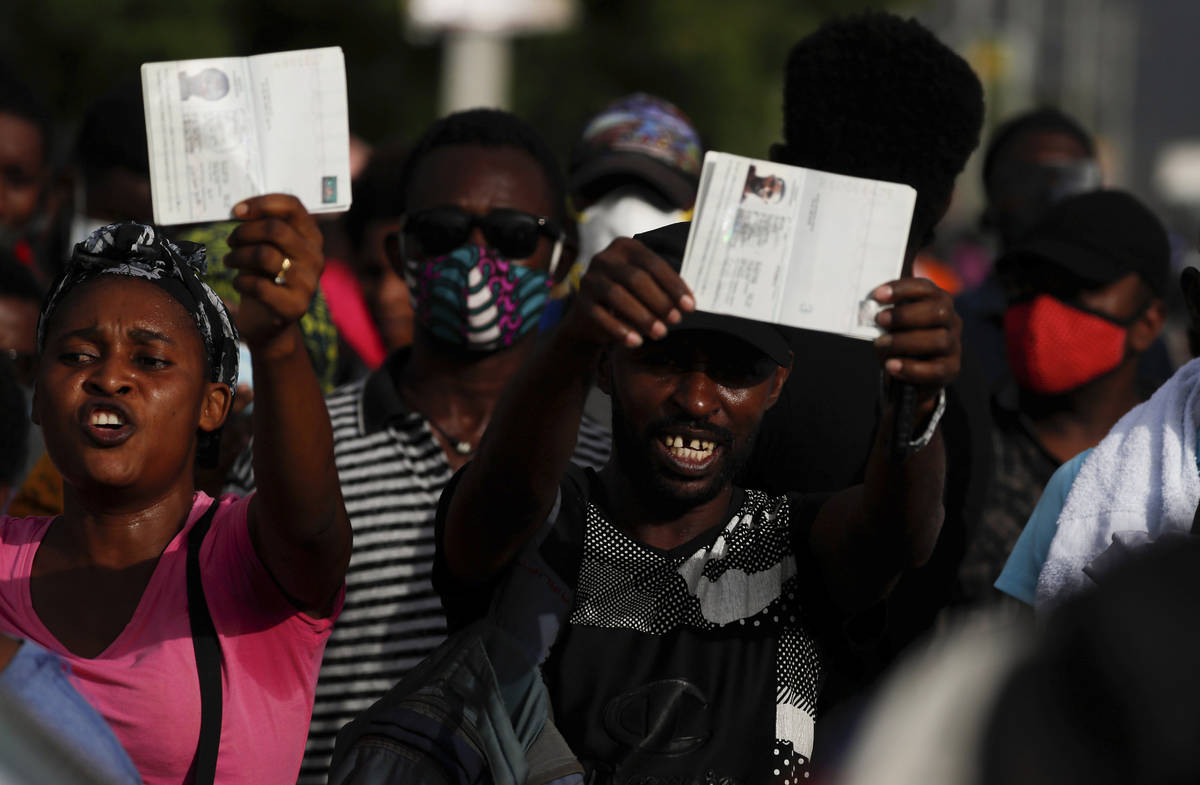"""Haitians wave their passports shouting """"Help, refugee,"""" as they gather outside the U. ..."""
