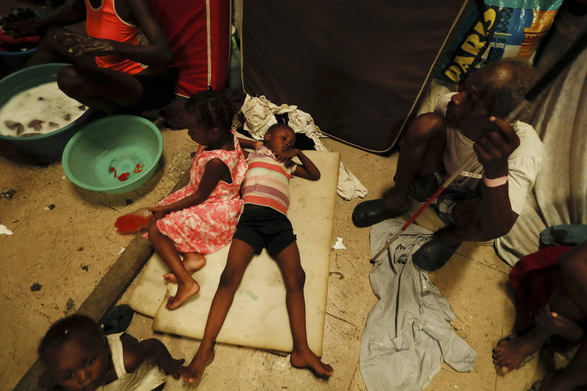 A boy lies on pieces of foam at a shelter for displaced Haitians, in Port-au-Prince, Haiti, Sat ...