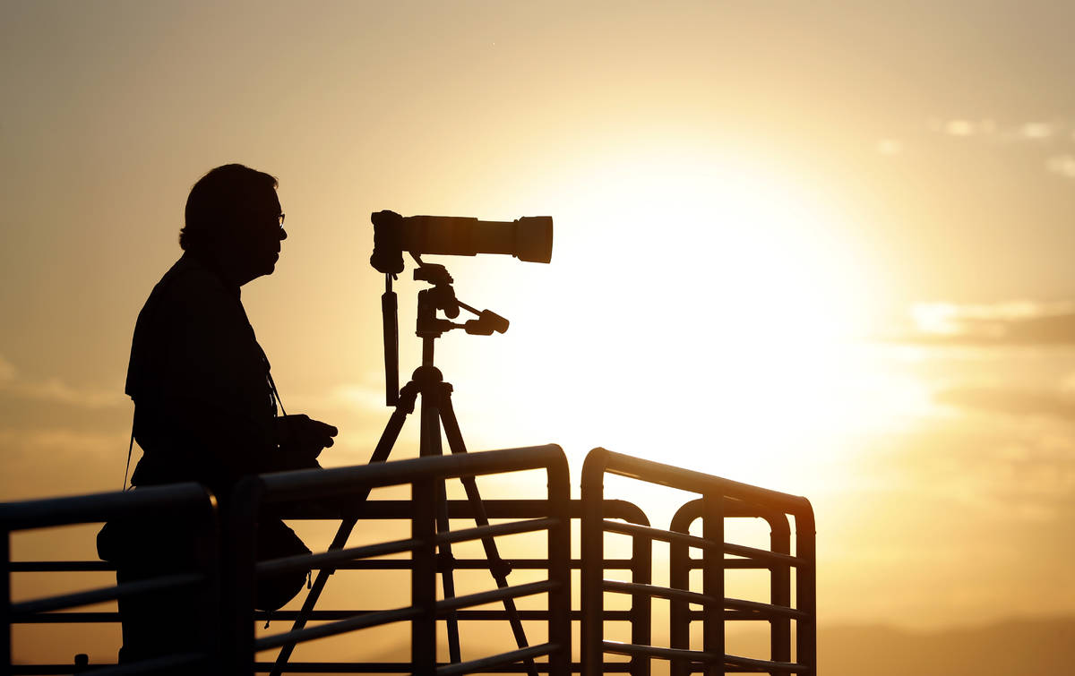 A photographer prepares his camera as the sun rises over Spaceport America before Virgin Galact ...