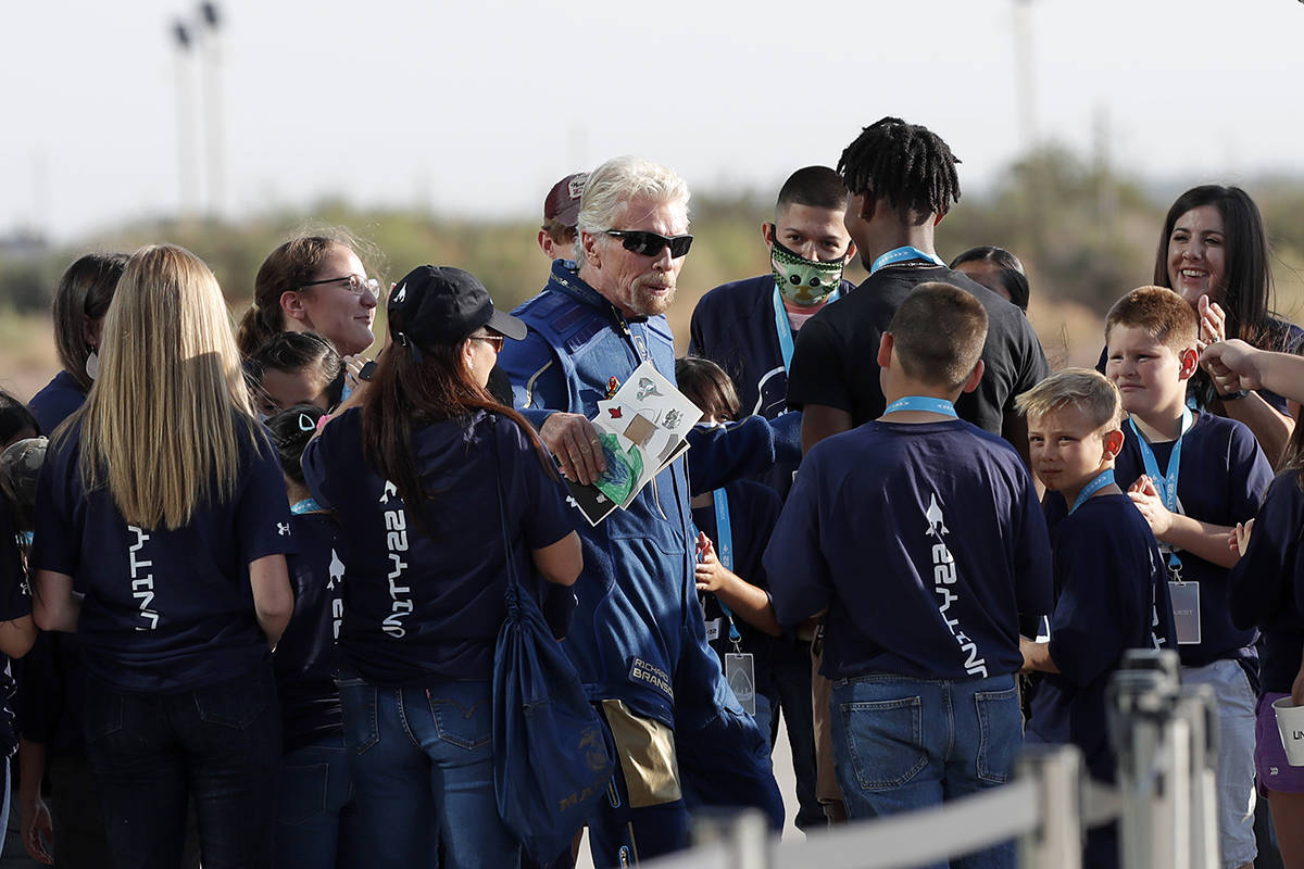 Virgin Galactic founder Richard Branson is greeted by school children before heading to board t ...