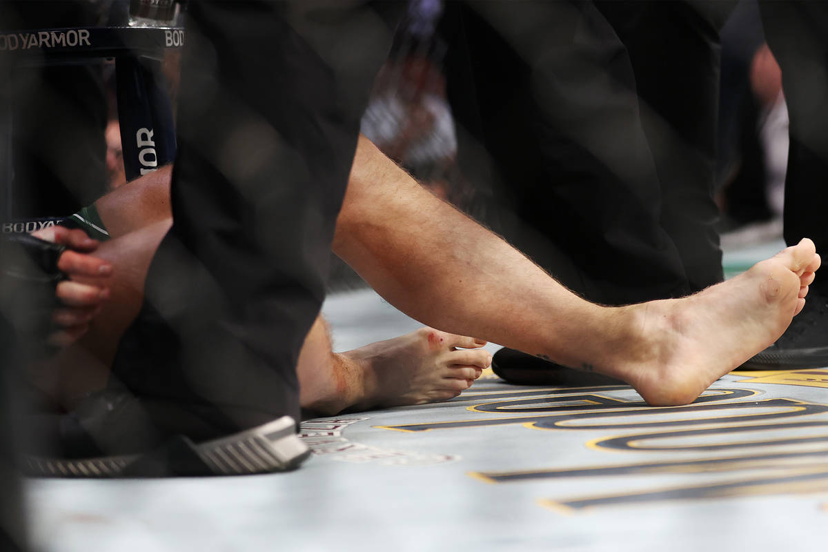 Conor McGregor receives assistance after hurting his foot in the first round of a lightweight b ...