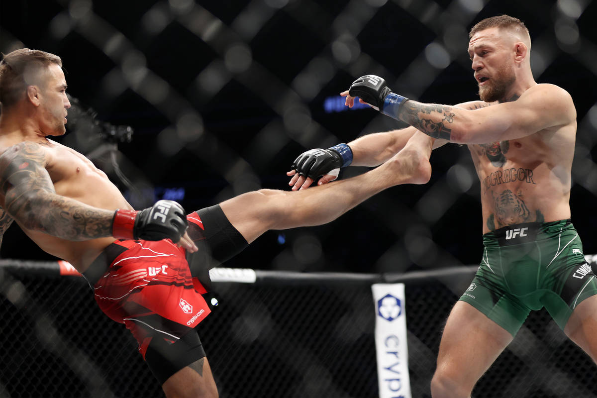 Dustin Poirier, left, throws a kick against Conor McGregor in the first round of a lightweight ...
