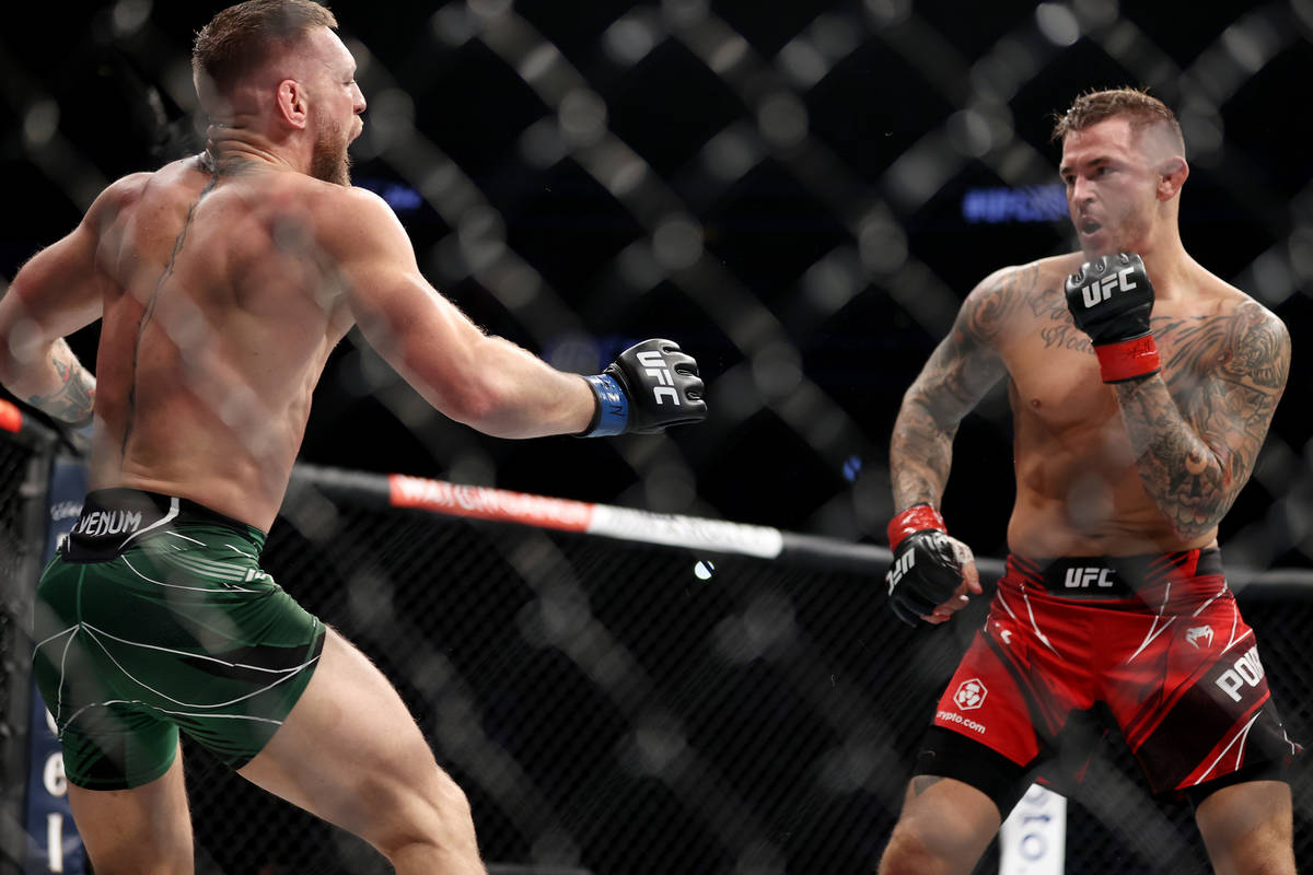Conor McGregor, left, reacts after hurting his foot in the first round of a lightweight bout ag ...