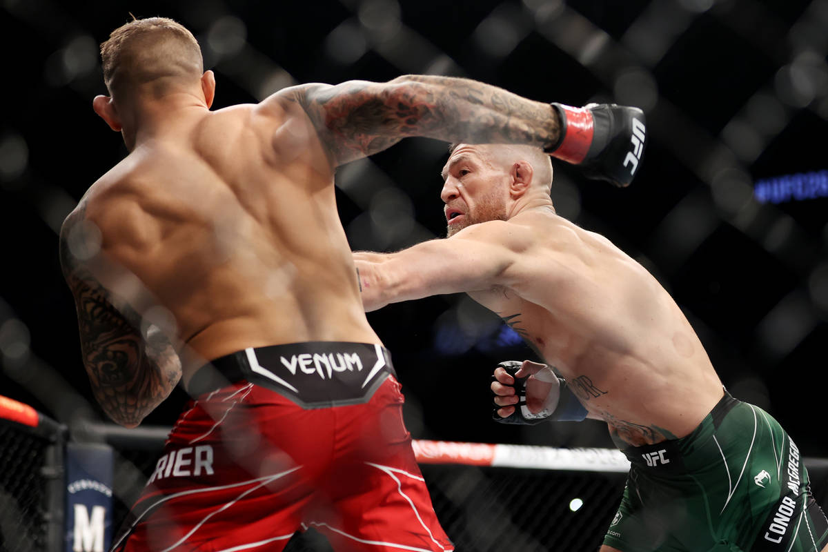 Conor McGregor, right, throws a punch against Dustin Poirier in the first round of a lightweigh ...