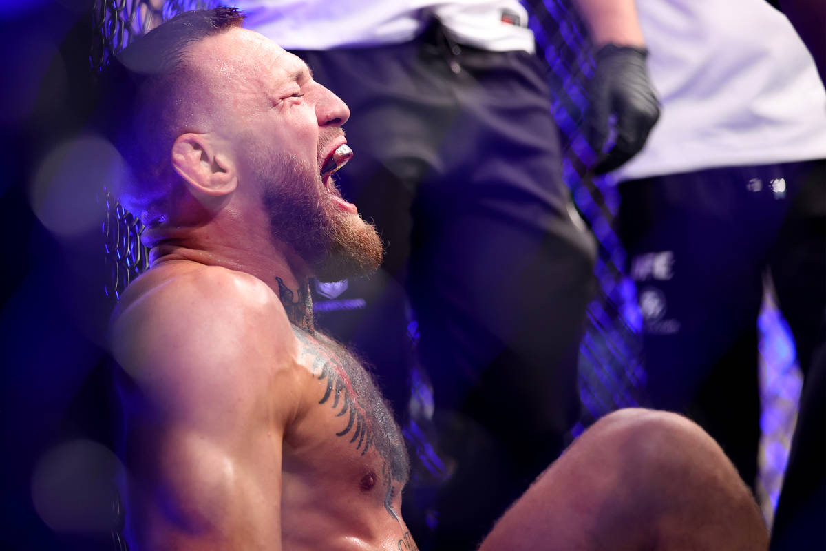 Conor McGregor yells in pain after hurting his foot in the first round of a lightweight bout ag ...