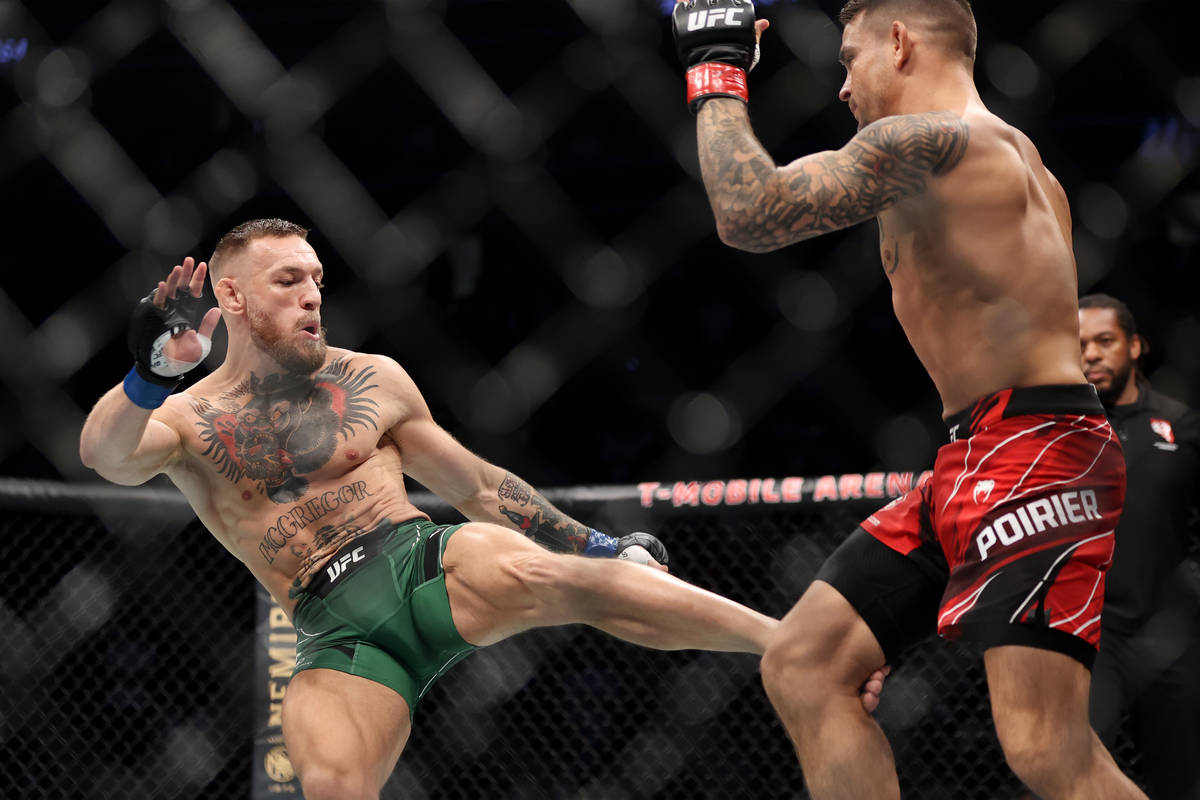Conor McGregor, left, kicks Dustin Poirier in the first round of a lightweight bout during the ...