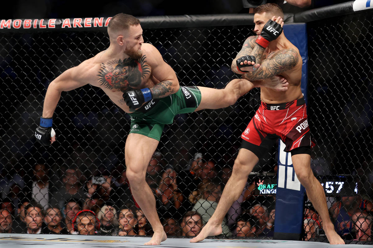 Conor McGregor, left, kicks Dustin Poirier in the first round of a lightweight bout against Dus ...