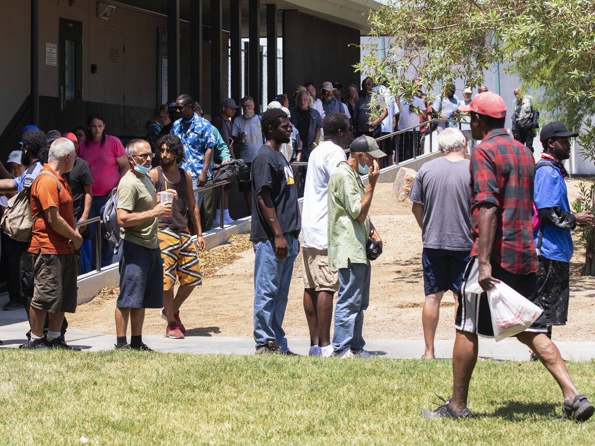 Clients wait in a queue to receive free food outside Dula Community Center, on Monday, July 12, ...
