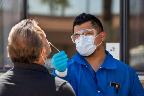 Jose Tirana conducts a COVID-19 test on a patient at Sahara West Urgent Care & Wellness on June ...