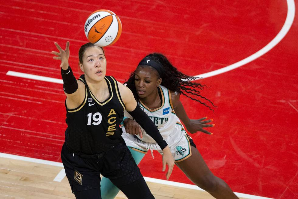 Las Vegas Aces center JiSu Park (19) reaches for control of the ball while New York Liberty for ...