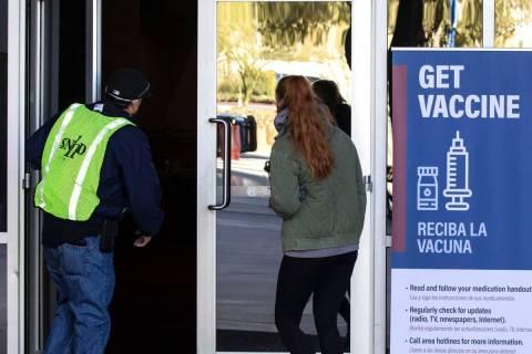 A FEMA volunteer leads a woman into the Las Vegas Convention Center's vaccine distribution area ...