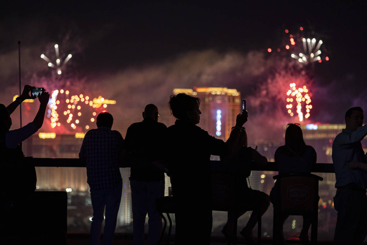 Spectators watch as fireworks explode over the Las Vegas Strip during a 4th of July Fireworks s ...