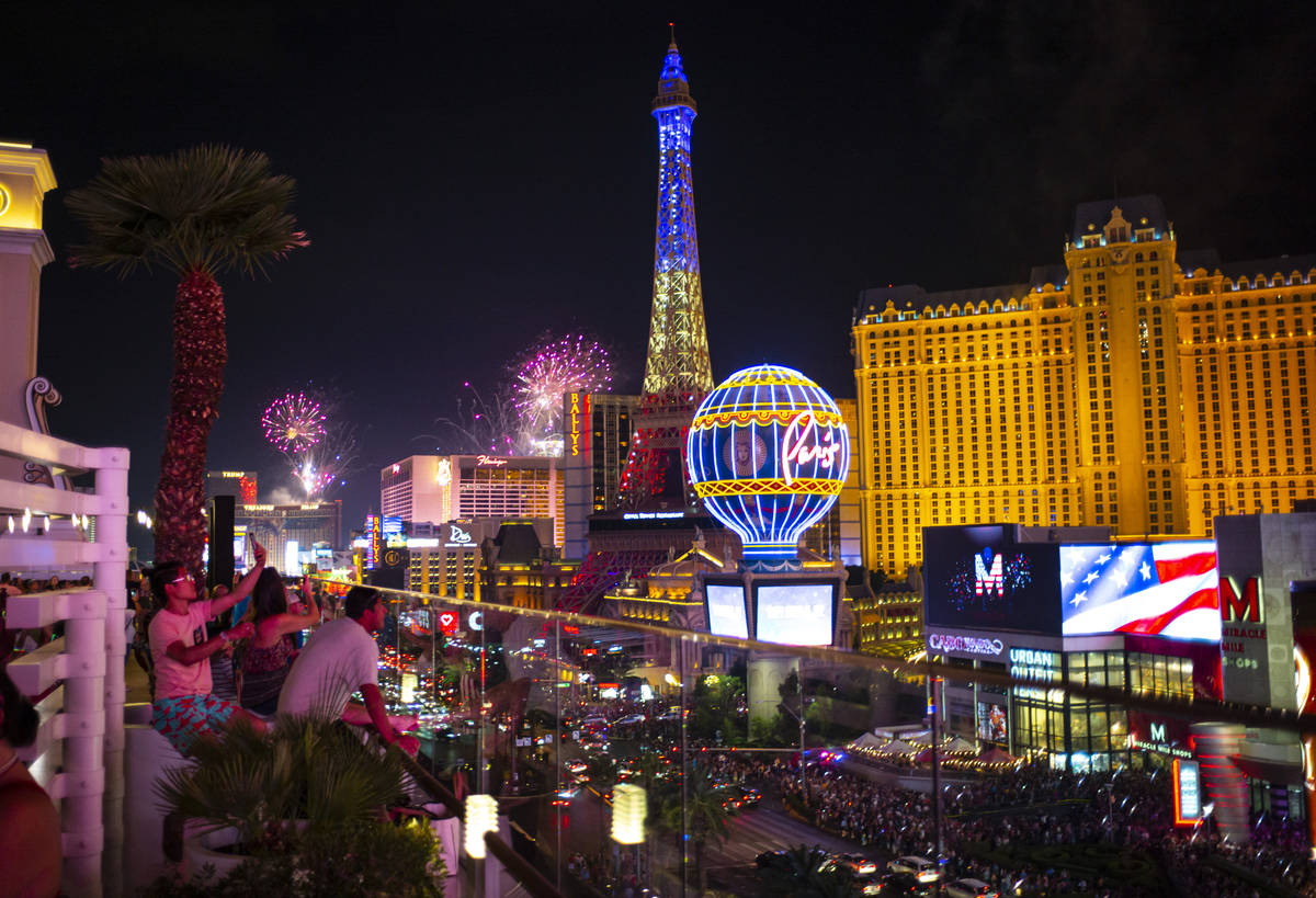 Fireworks go off along the Las Vegas Strip as people watch from the Boulevard Pool at The Cosmo ...