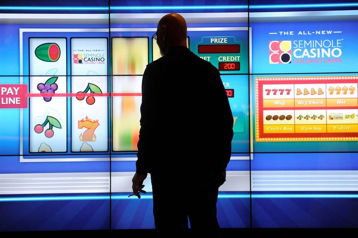 A man plays a large slot machine at Seminole Casino Coconut Creek in Florida in February 2012. ...
