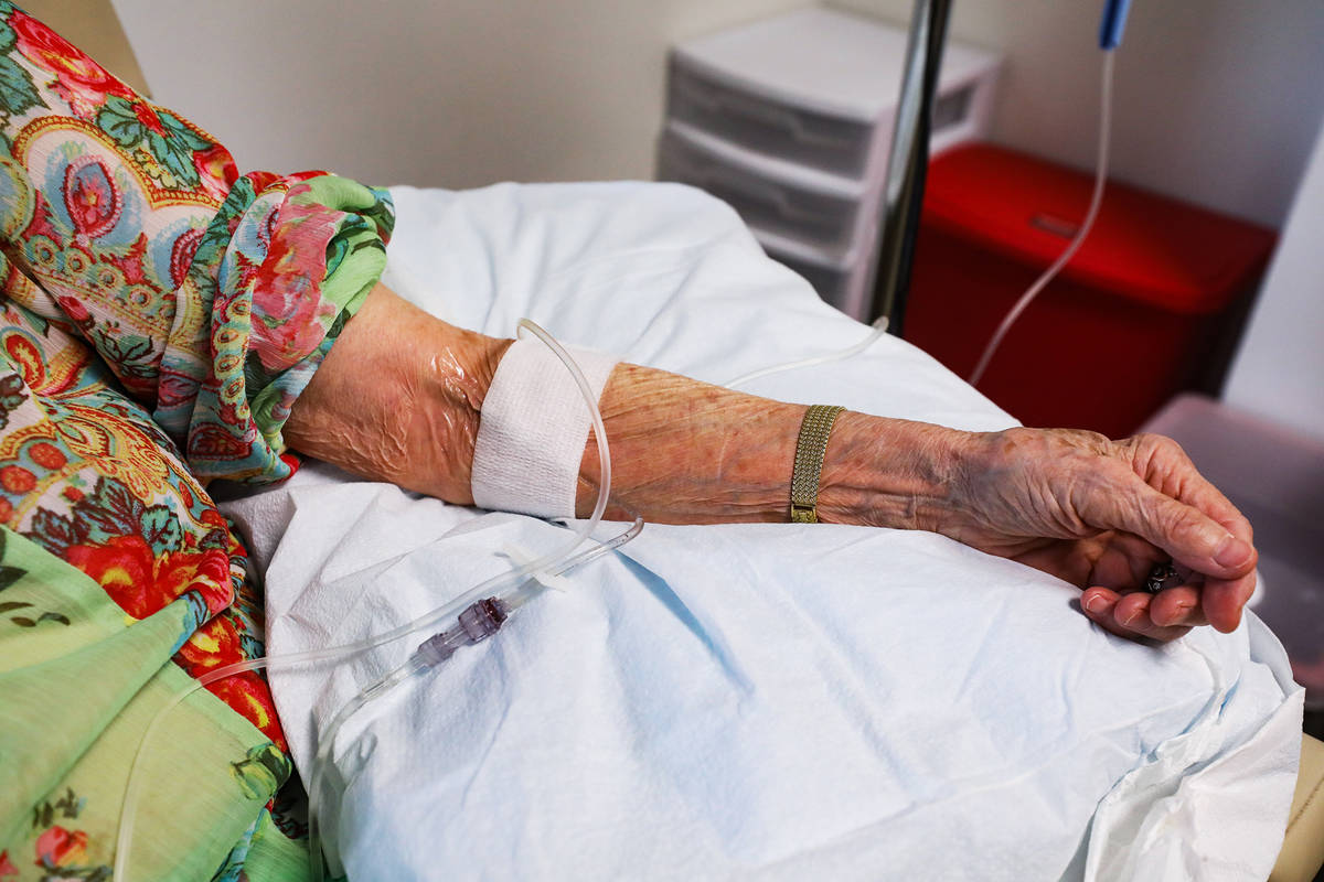 Judy Robinson's arm shows the infusion of aducanumab, a drug designed by Biogen to slow ...