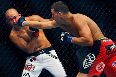 Nick Diaz, right, lands a right hand to the face of BJ Penn during the main event at UFC 137 at ...