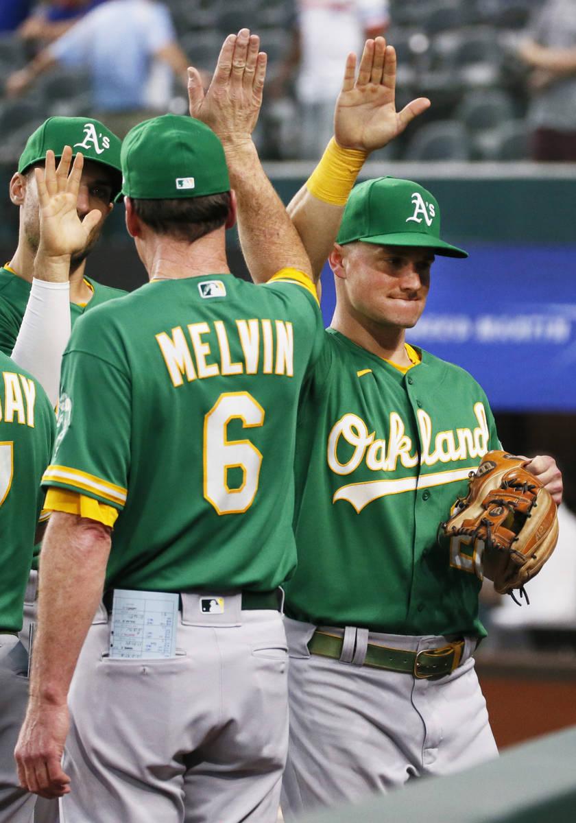 Oakland Athletics manager Bob Melvin, left, high fives Matt Chapman, right, following a basebal ...