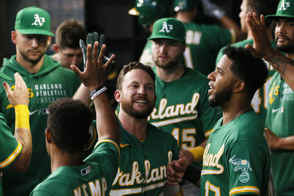Oakland Athletics' Jed Lowrie is greeted in the dugout after hitting a solo home run against th ...