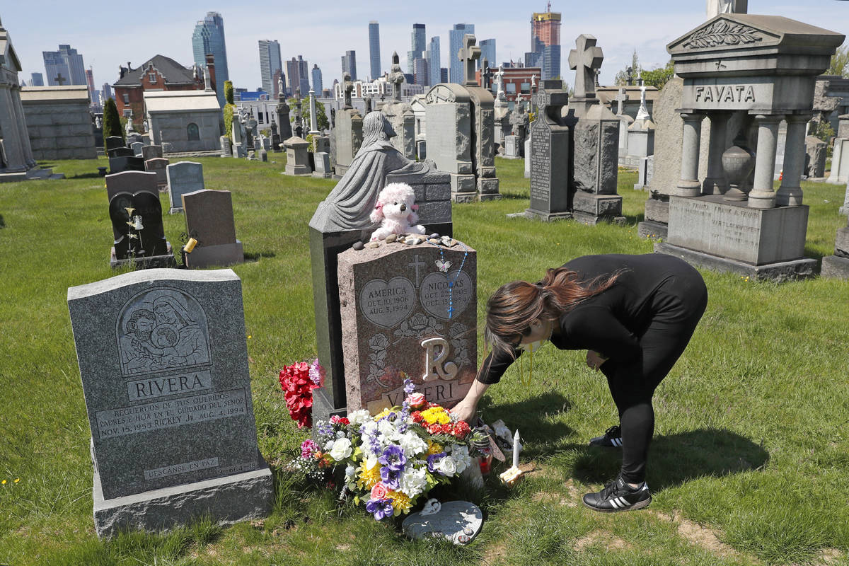 In this Sunday, May 10, 2020, file photo, Sharon Rivera adjusts flowers and other items left at ...