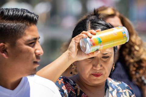 A pedestrian places a can of soda on her forehead to cool herself as she walks along Las Vegas ...