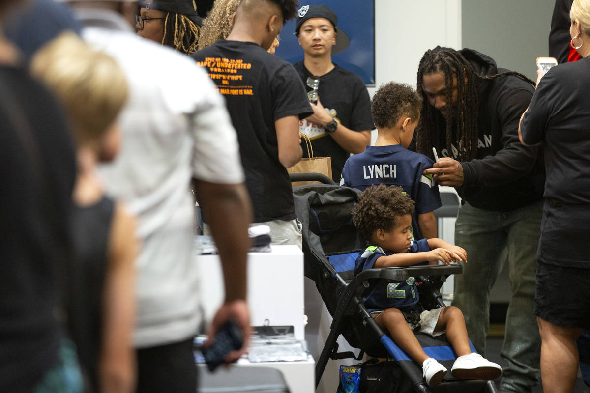 NFL running back Marshawn Lynch signs a jersey for Romeo Havard, 5, among fans and customers at ...