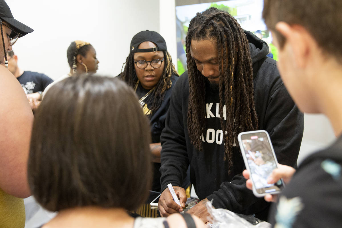 NFL running back Marshawn Lynch signs merchandise for fans and customers at the opening of his ...