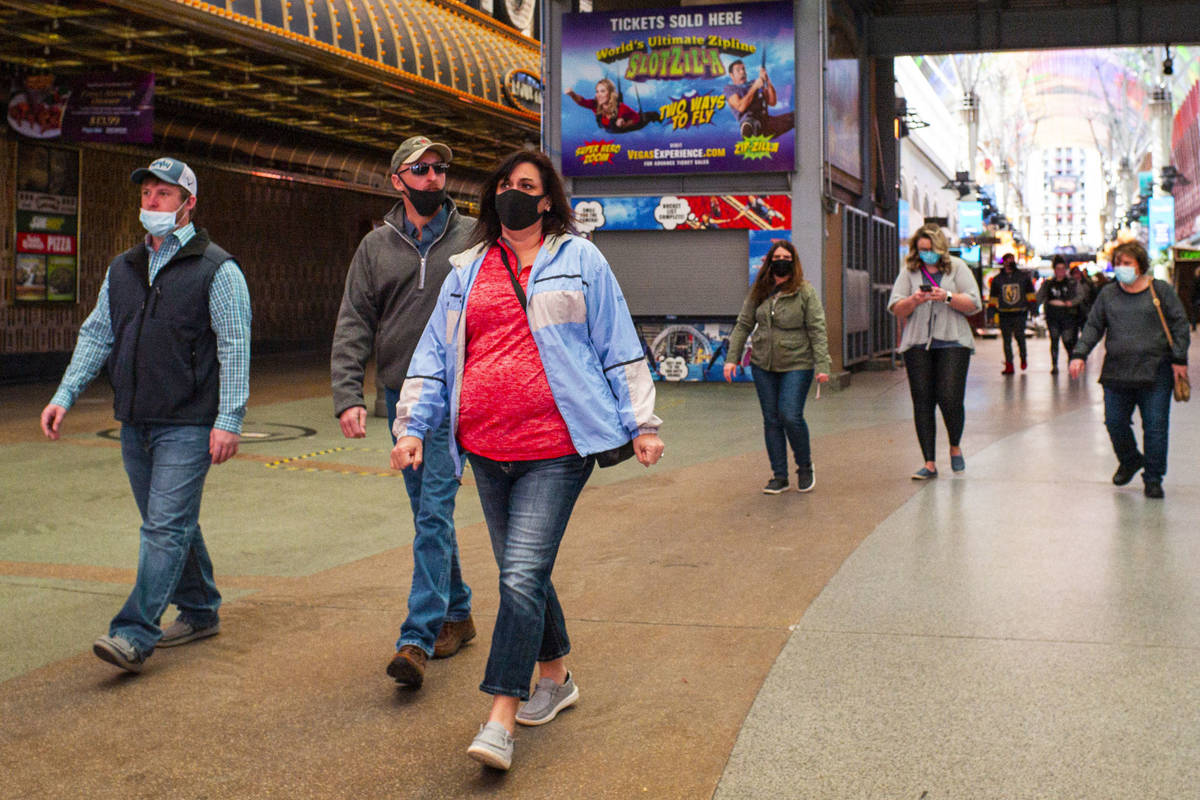 People wearing face masks, including two worn improperly below the nose, are seen walking along ...