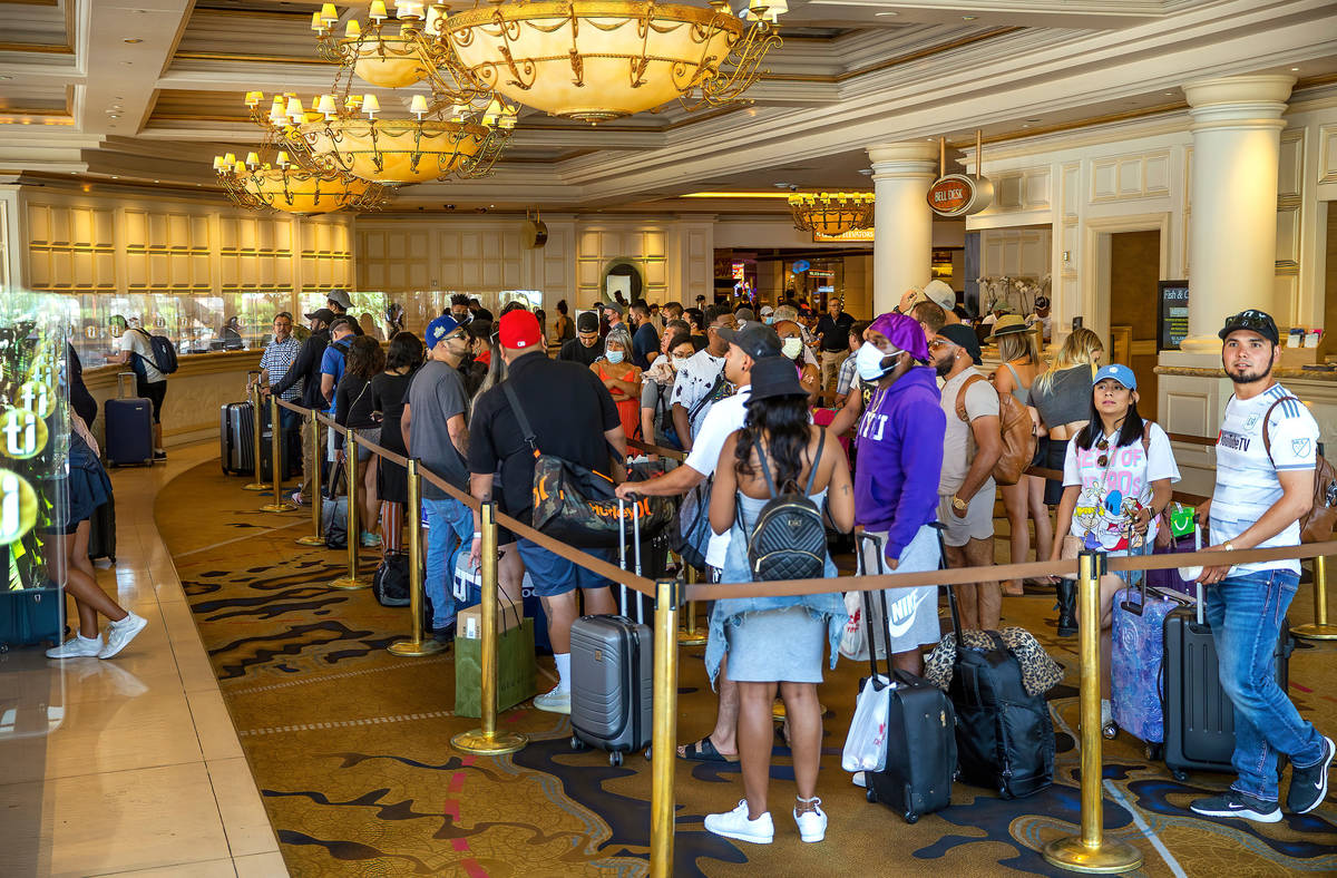 People stand in line to check in at Treasure Island, a large percentage not wearing mask, on Fr ...