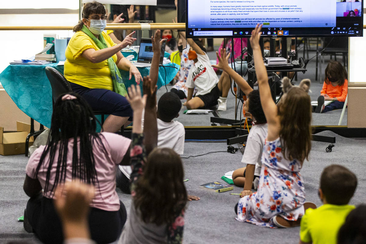 Students raise their hands as learning guide Tammy Slank, left, leads a discussion during a thi ...