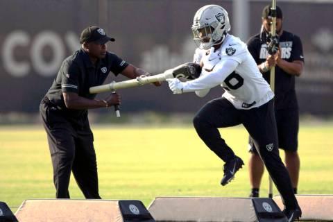 Raiders running back Josh Jacobs (28) runs with the football as running back coach Kirby Wilson ...