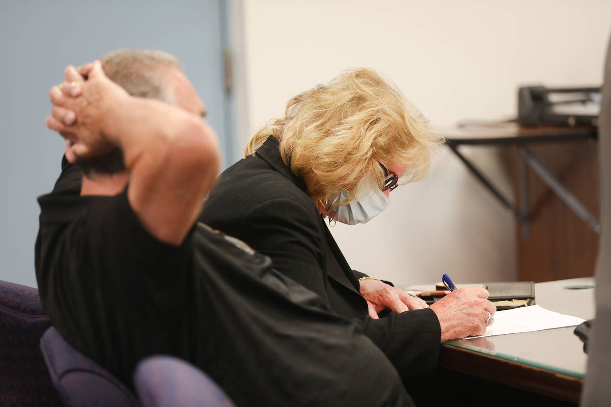 Patricia Chappuis signs a document to waive her right to a preliminary hearing next to her husb ...