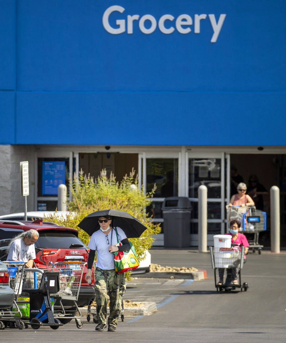 Shoppers make their way through a Walmart parking lot, most not wearing masks anymore on Friday ...