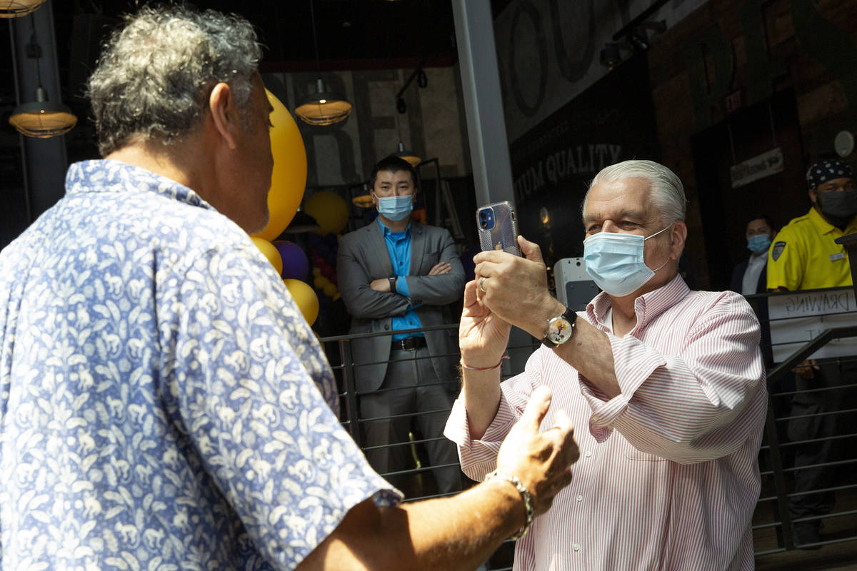 Gov. Steve Sisolak takes a video of comedian Brad Garrett during a pop-up vaccination clinic ho ...