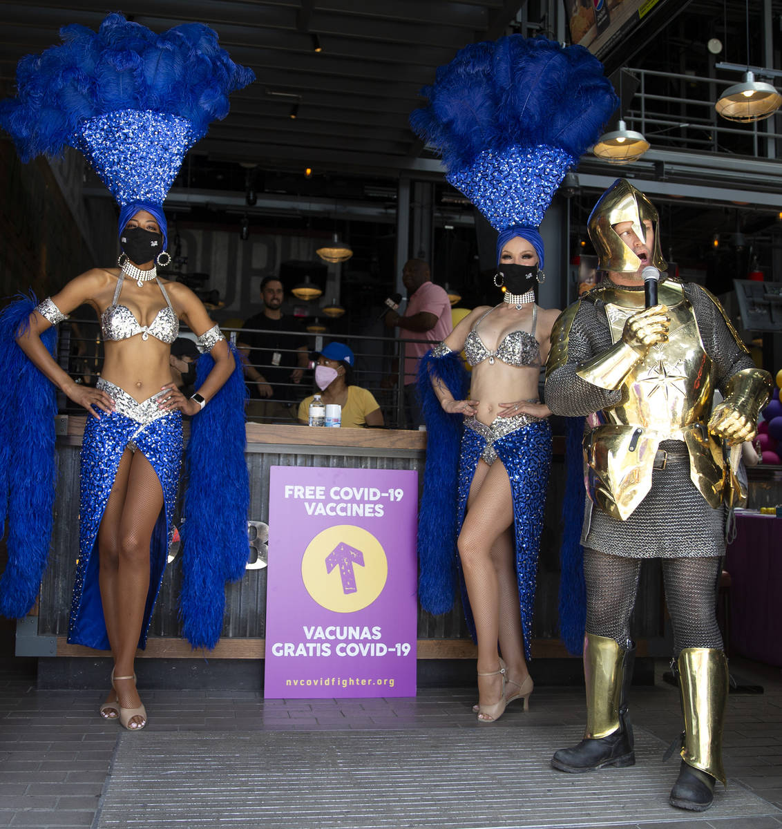 Showgirls and a Vegas Golden Knight encourage passersby to get a free COVID-19 vaccination duri ...